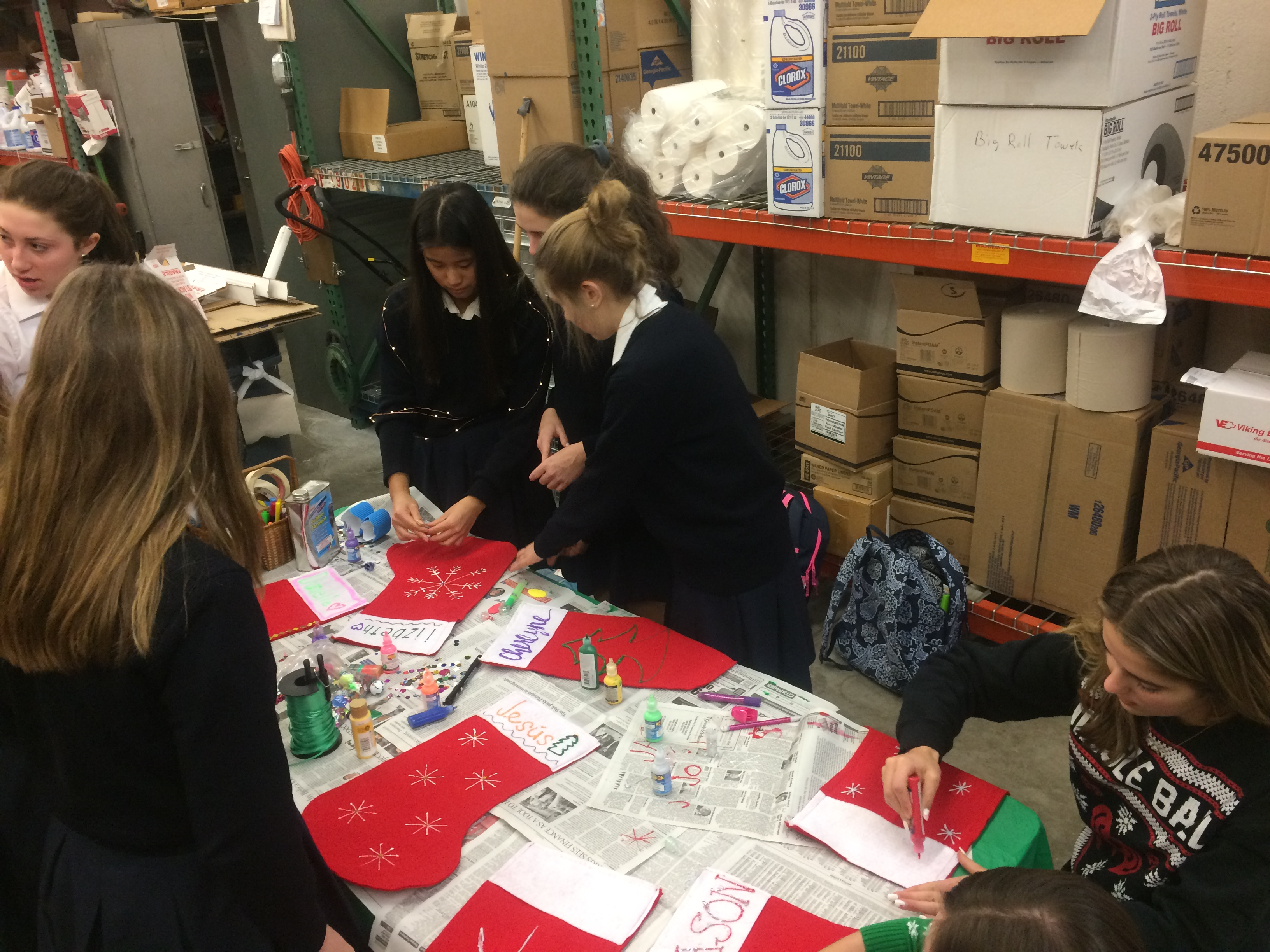 Students work on sewing Christmas stockings